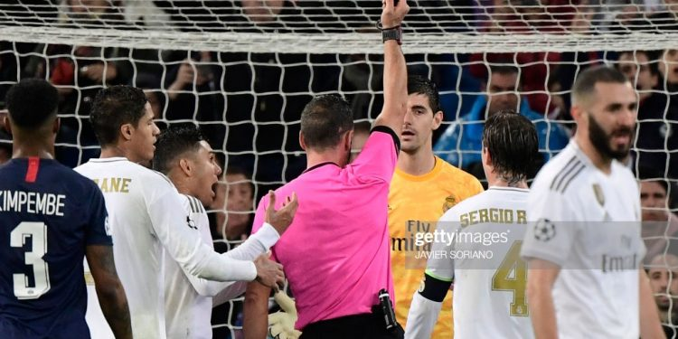 Portuguese referee Artur Dias hands a red card to Real Madrid's Belgian goalkeeper Thibaut Courtois during the UEFA Champions League group A football match against Paris Saint-Germain FC at the Santiago Bernabeu stadium in Madrid on November 26, 2019. (Photo by JAVIER SORIANO / AFP) (Photo by JAVIER SORIANO/AFP via Getty Images)
