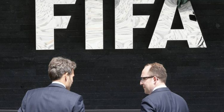 """Two men talk to each other in front of the FIFA logo at the FIFA headquarters in Zurich, Switzerland, Wednesday, May 27, 2015. Swiss prosecutors opened criminal proceedings into FIFA's awarding of the 2018 and 2022 World Cups, only hours after seven soccer officials were arrested Wednesday pending extradition to the U.S. in a separate probe of """"rampant, systemic, and deep-rooted"""" corruption. (AP Photo/Michael Probst)"""