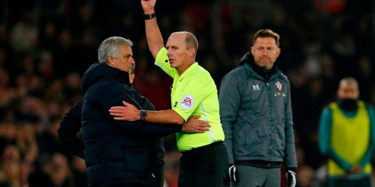 Southampton's Austrian manager Ralph Hasenhuttl (R) looks on a English referee Mike Dean shows Tottenham Hotspur's Portuguese head coach Jose Mourinho (L) a yellow card during the English Premier League football match between Southampton and Tottenham at St Mary's Stadium in Southampton, southern England on January 1, 2020. (Photo by Adrian DENNIS / AFP) / RESTRICTED TO EDITORIAL USE. No use with unauthorized audio, video, data, fixture lists, club/league logos or 'live' services. Online in-match use limited to 120 images. An additional 40 images may be used in extra time. No video emulation. Social media in-match use limited to 120 images. An additional 40 images may be used in extra time. No use in betting publications, games or single club/league/player publications. / (Photo by ADRIAN DENNIS/AFP via Getty Images)