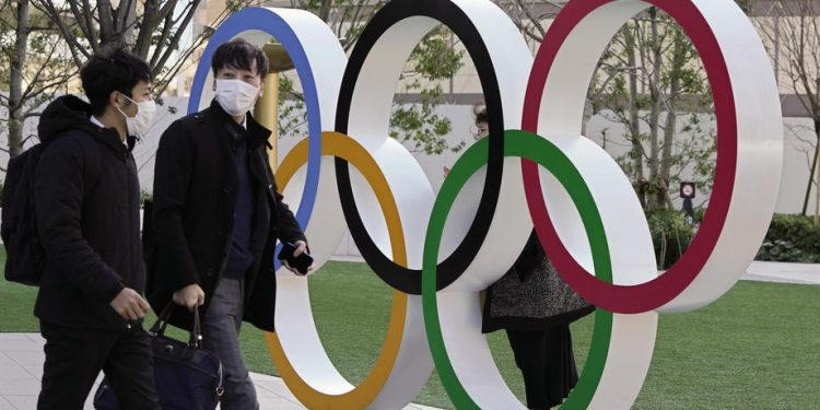 epa08251597 Visitors wearing face masks walk past the Olympic Rings monument in front of the Japan Olympic Committee headquarters near the new National Stadium, venue of the Opening and Closing Ceremony of the Tokyo 2020 Summer Olympic Games, in Tokyo, Japan, 27 February 2020. Preparations for the Tokyo 2020 Olympic Games, scheduled to start on 24 July 2020, continue as planned despite the spreading Covid-19 coronavirus outbreak, organizers confirmed.  EPA-EFE/KIMIMASA MAYAMA
