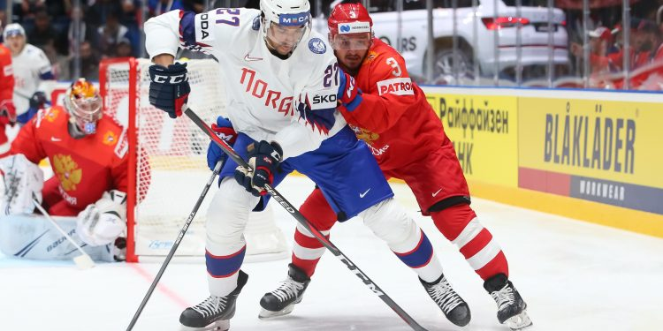BRATISLAVA, SLOVAKIA - MAY10: Norway's Andreas Martinsen #27 plays the puck while Russia's Dinar Khafizullin #3 defends during preliminary round action at the 2019 IIHF Ice Hockey World Championship at Ondrej Nepela Arena on May 10, 2019 in Bratislava, Slovakia. (Photo by Andre Ringuette/HHOF-IIHF Images)