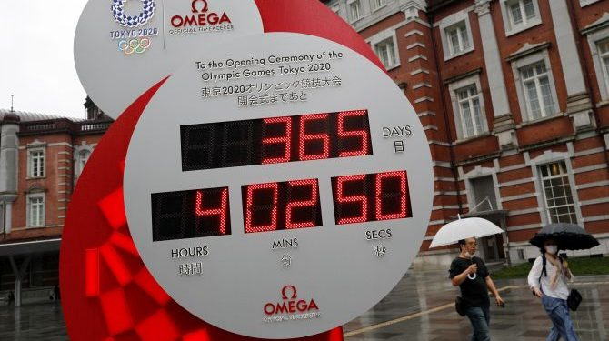 Passersby wearing protective face masks walk past a countdown clock for the Tokyo 2020 Olympic Games, on the day to mark the one-year countdown to the summer games that have been postponed to 2021 due to the coronavirus disease (COVID-19) outbreak, in Tokyo, Japan July 23, 2020.  REUTERS/Issei Kato