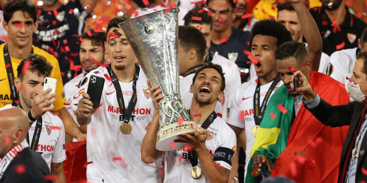 Sevilla's Spanish midfielder Jesus Navas holds the trophy as Sevilla's players celebrate  after winning the UEFA Europa League final football match Sevilla v Inter Milan on August 21, 2020, in Cologne, western Germany. (Photo by Lars Baron / POOL / AFP) (Photo by LARS BARON/POOL/AFP via Getty Images)