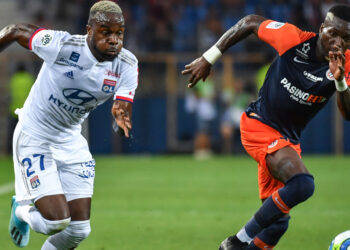 Lyon's Ivorian forward Maxwell Gnaly Cornet (L) vies with Montpellier's Cameroon defender Ambroise Oyongo during the French L1 football match between Montpellier Herault SC and Olympique Lyonnais at the Mosson stadium in Montpellier, southern France, on August 27, 2019. (Photo by PASCAL GUYOT / AFP)