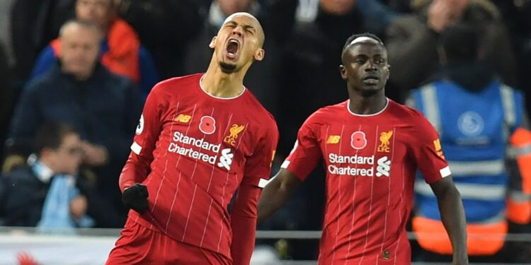 Liverpool's Brazilian midfielder Fabinho (L) celebrates after scoring the opening goal of the English Premier League football match between Liverpool and Manchester City at Anfield in Liverpool, north west England on November 10, 2019. (Photo by Paul ELLIS / AFP) / RESTRICTED TO EDITORIAL USE. No use with unauthorized audio, video, data, fixture lists, club/league logos or 'live' services. Online in-match use limited to 120 images. An additional 40 images may be used in extra time. No video emulation. Social media in-match use limited to 120 images. An additional 40 images may be used in extra time. No use in betting publications, games or single club/league/player publications. /  (Photo by PAUL ELLIS/AFP via Getty Images)