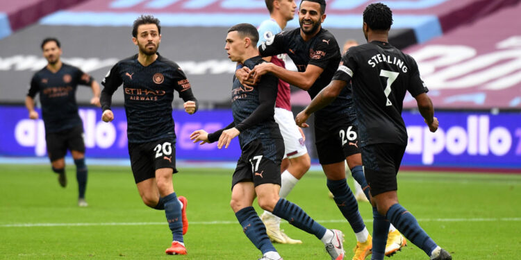 LONDON, ENGLAND - OCTOBER 24: Phil Foden of Manchester City celebrates with his team after scoring his sides first goal during the Premier League match between West Ham United and Manchester City at London Stadium on October 24, 2020 in London, England. Sporting stadiums around the UK remain under strict restrictions due to the Coronavirus Pandemic as Government social distancing laws prohibit fans inside venues resulting in games being played behind closed doors. (Photo by Justin Tallis - Pool/Getty Images)