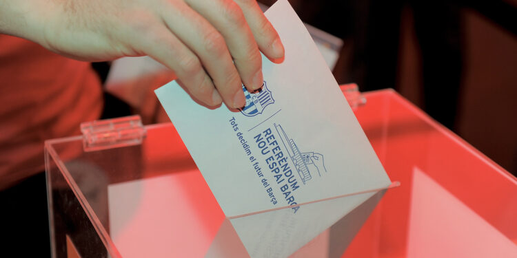 A Barcelona football club partner casts his ballot at the Camp Nou stadium in Barcelona on April 5, 2014 during a referendum by Barcelona FC partners for the renovation of the club's stadium. The polls opened at 0900 local ( 0700 GMT ) and four hours later 11,730 voting members of the118,580 had voted on wheter or not to expand capacity to 105,000 seats and a set roof over the existing structure. AFP PHOTO/ JOSEP LAGO        (Photo credit should read JOSEP LAGO/AFP via Getty Images)