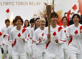 Tokyo 2020 Olympic Torch Relay Grand Start torchbearer Nadeshiko Japan, Japan's women's national soccer team, leads the torch relay in Naraha, Fukushima prefecture, Japan March 25, 2021. REUTERS/Kim Kyung-Hoon/Pool