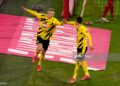 MUNICH, GERMANY - MARCH 06: Erling Haaland of Borussia Dortmund  celebrates with teammate Thorgan Hazard  after scoring their team's second goal  during the Bundesliga match between FC Bayern Muenchen and Borussia Dortmund at Allianz Arena on March 06, 2021 in Munich, Germany. Sporting stadiums around Germany remain under strict restrictions due to the Coronavirus Pandemic as Government social distancing laws prohibit fans inside venues resulting in games being played behind closed doors. (Photo by Günter Schiffmann - Pool/Getty Images)