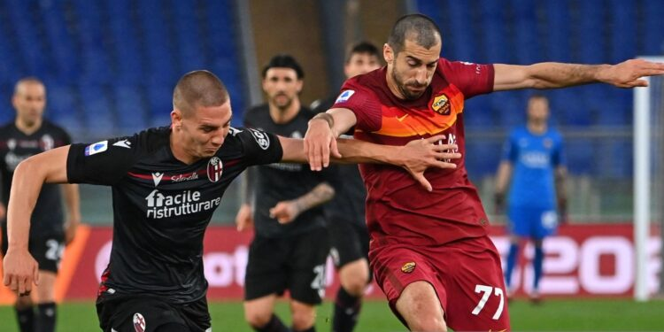 Bologna's Bulgarian defender Valentin Antov (L) and Roma's Armenian midfielder Henrikh Mkhitaryan go for the ball during the Italian Serie A football match AS Rome vs Bologna on April 11, 2021 at the Olympic stadium in Rome. (Photo by ANDREAS SOLARO / AFP) (Photo by ANDREAS SOLARO/AFP via Getty Images)