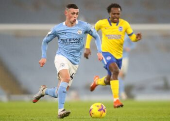 Manchester City's English midfielder Phil Foden (L) runs with the ball during the English Premier League football match between Manchester City and Brighton and Hove Albion at the Etihad Stadium in Manchester, north west England, on January 13, 2021. (Photo by Clive Brunskill / POOL / AFP) / RESTRICTED TO EDITORIAL USE. No use with unauthorized audio, video, data, fixture lists, club/league logos or 'live' services. Online in-match use limited to 120 images. An additional 40 images may be used in extra time. No video emulation. Social media in-match use limited to 120 images. An additional 40 images may be used in extra time. No use in betting publications, games or single club/league/player publications. /  (Photo by CLIVE BRUNSKILL/POOL/AFP via Getty Images)