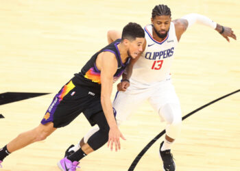 Jan 3, 2021; Phoenix, Arizona, USA; Phoenix Suns guard Devin Booker (1) dribbles against Los Angeles Clippers guard Paul George (13) in the second half at Phoenix Suns Arena. Mandatory Credit: Billy Hardiman-USA TODAY Sports