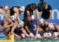 United States head coach Adam Krikorian, kneeling at center, talks with his team during a preliminary round women's water polo match against China at the 2020 Summer Olympics, Monday, July 26, 2021, in Tokyo, Japan. (AP Photo/Mark Humphrey)